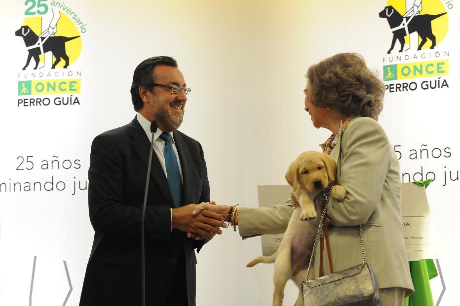 SM la Reina Doña Sofía, con un cahorro de futuro perro guía en sus brazos, saluda a Miguel Carballeda, presidente de la ONCE y su Fundación.jpg