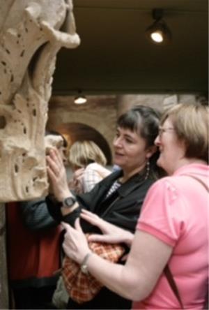 Voluntario acompaña persona ciega visita museo.jpg