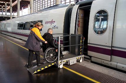 Usuario en silla de ruedas atendido por asistente servicio Atendo en el acceso al tren